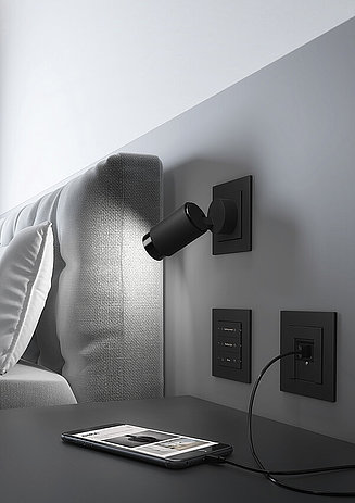 Black Gira Plug and light shown in a bedroom
